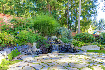 Backyard fountain with stone and shrubs