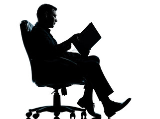 one business man sitting in armchair reading ancient book silhou