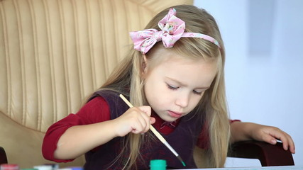 Girl learns to paint with a brush
