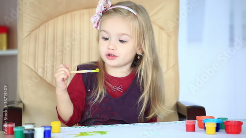 Girl learns to paint with a brush-1