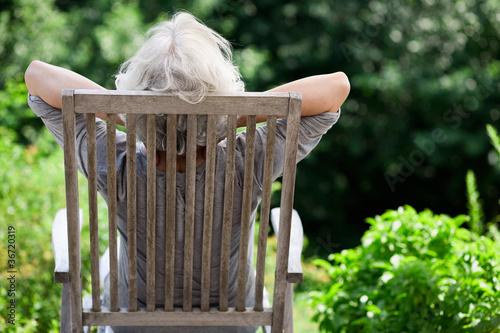 Leinwanddruck Bild grauhaarige Frau entspannt im Garten