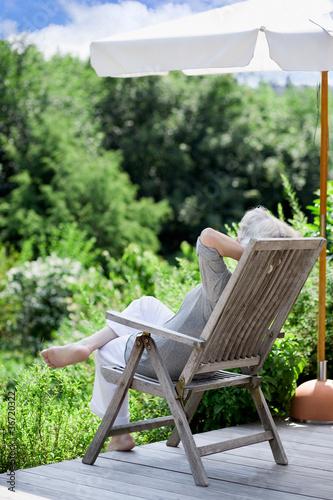 grauhaarige Frau entspannt im Garten