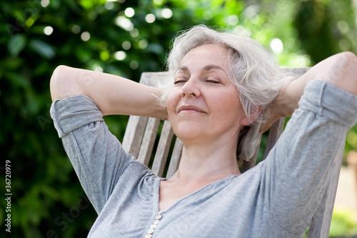 grauhaarige Frau entspannt auf der Sonnenterrasse