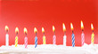 Leinwanddruck Bild - 10 lit birthday candles in bright colors with red background