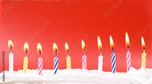 10 lit birthday candles in bright colors with red background - 36721320