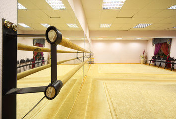 Empty light ballet class with ballet lathe and thick carpet