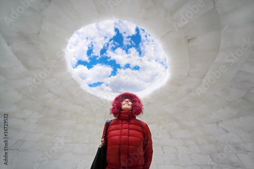 young woman in red jacket standing inside igloo at winter