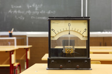 Educational galvanometer with not real number 555 on yellow desk