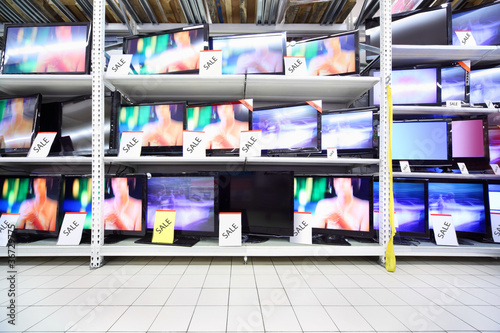 Plasma TVs with big diagonal stand on shelves in large shop