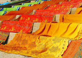 Bright orange and red saris draped on stairs to dry in the sun