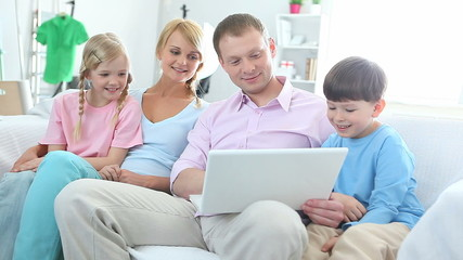 Family with two kids surfing internet and smiling