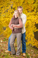 Autumn love couple hugging happy in park