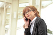 Portrait of pretty business leader talking by mobile phone with