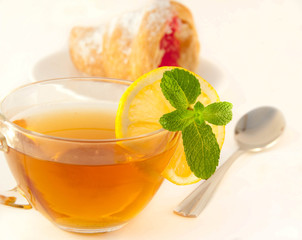 Croissant with jam and tea with a lemon and mint