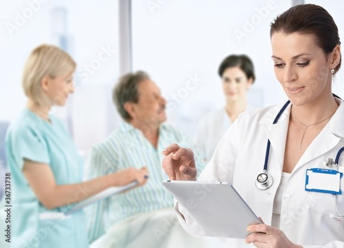 Doctor making notes at patients bed