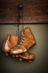 Vintage football boots hanging on a locker room
