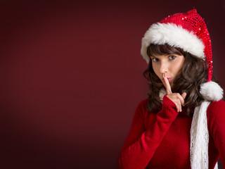 Wihnachtsfrau mit Finger vor Mund