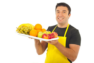 Happy market worker holding fruits
