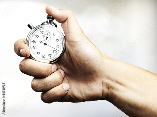 Leinwandbild Motiv hand holding stopwatch
