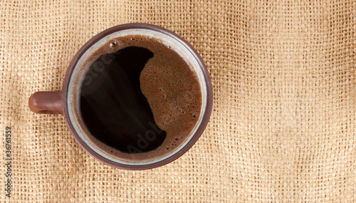 cup of coffee standing on sackcloth