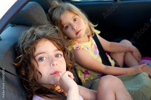 little girls inside car eating candy stick