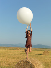 happy woman jumping white balloon hay stack