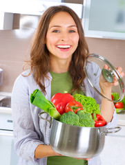 Beautiful Young Woman cooking fresh Vegetables