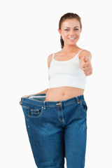 Portrait of a woman wearing too large jeans with the thumb up