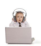 Funny child playing with laptop and listening to music in headph