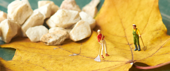 Miniature figurine  using a rake to clean up of the fallen leave