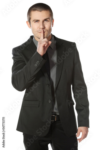 Business man with finger on lips asking for silence