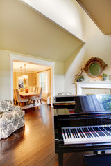 Cream yellow living room with grand piano and dining