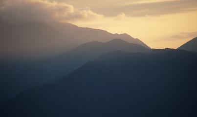 Tramonto, montagne e fasci di luce