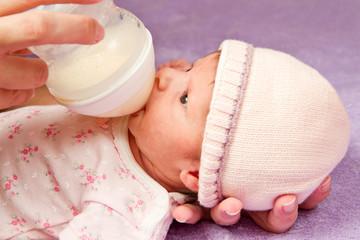 bambina che mangia dal biberon