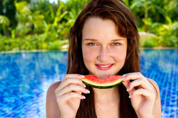 An young and attractive woman eating watermelon by the pool