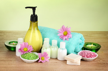 Hotel amenities kit on wooden table on green background