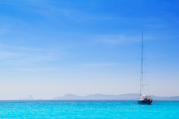 Ibiza mountains with sailboat from Formentera