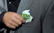 Hand steckt 100 Euro in Jacket