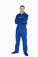 Smiling young mechanic in boiler suit with arms folded