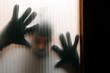 Einbrecher hinter Glasscheibe