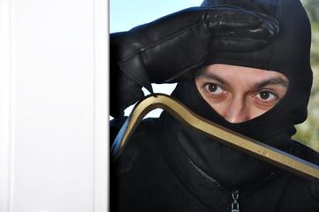 Einbrecher schaut durch Fenster