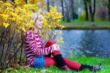 Blond woman sitting on the river bank