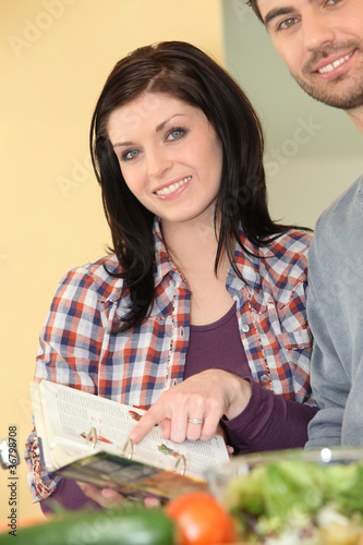 brunette and man in kitchen preparing recipe
