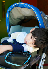 Disabled five year old boy in wheelchair waiting at school