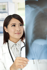 asian Doctor reviewing x-rays in doctor office
