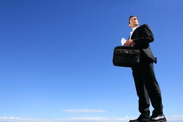 Smart businessman in front of blue sky