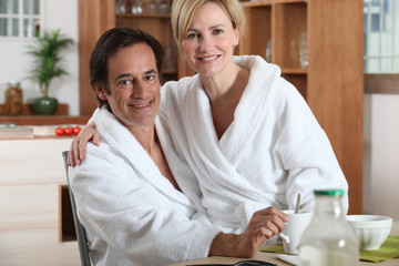 Couple having breakfast in towelling robes
