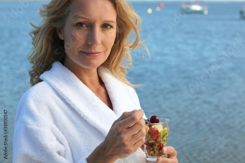 Smiling woman in toweling robe eating fruit salad
