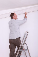 Decorator fitting coving to a ceiling