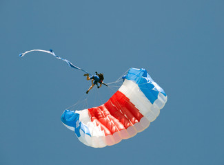 Skydiver hanging on parachute in air